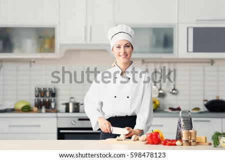 Female chef cutting mushrooms on wooden board in kitchen