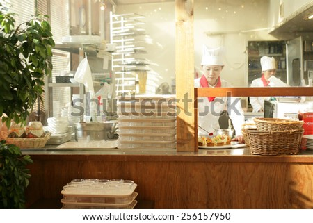 Female chef decorating a tart with a slice of strawberry and a chef standing in the background - stock photo