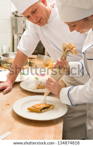 Female chef decorating cake with whipped cream using piping technique - stock photo