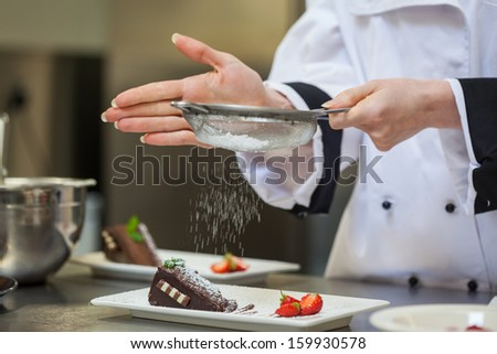Female chef finishing a dessert plate with icing sugar - stock photo