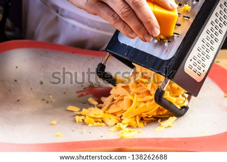 Female chef hand grating cheddar cheese on metal grater, onto plastic cutting board - stock photo