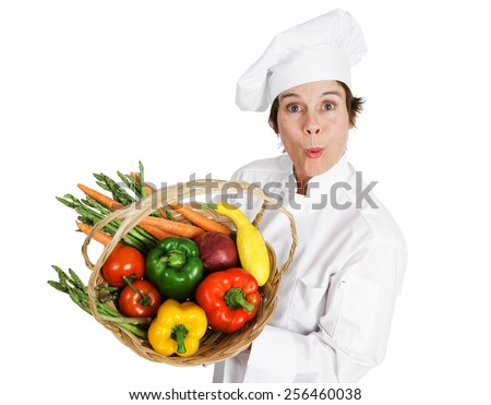 Female chef holding a basket of fresh organic, locally sourced vegetables.  Isolated on white.   - stock photo