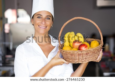 Female chef holding a basket with fruits - stock photo