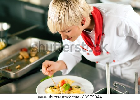 Female Chef in a restaurant or hotel kitchen cooking delicious food, both are finishing the dishes