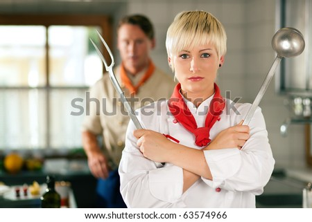 Female Chef in a restaurant or hotel kitchen posing with kitchen gear, in the background another chef - stock photo