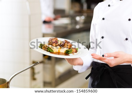 Female Chef in hotel or restaurant kitchen cooking, only hands to be seen, she is presenting a dish - stock photo
