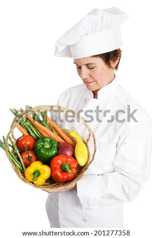 Female chef inspecting a basket of fresh vegetables.  Isolated on white.   - stock photo