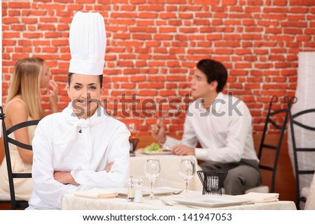female chef posing in restaurant with couple dining in background