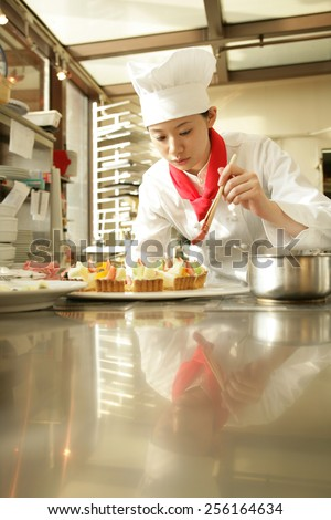 Female chef preparing a strawberry tart in a restaurant - stock photo