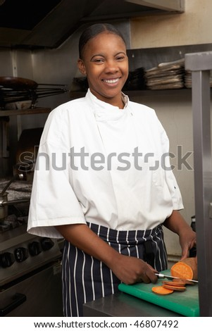 Female Chef Preparing Vegetables In Restaurant Kitchen - stock photo