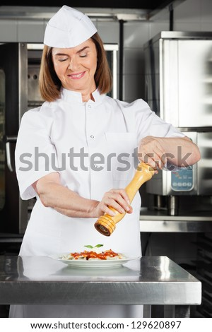 Female chef seasoning dish with peppermill at restaurant kitchen counter