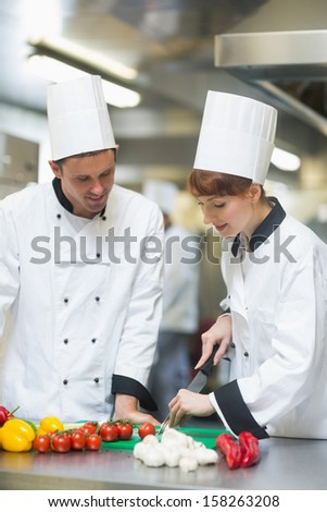 Female chef slicing vegetables being watched by her colleague