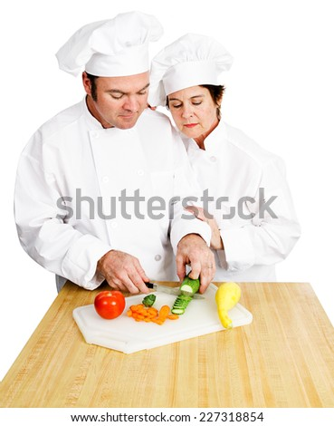 Female chef watches her male student chop vegetables on a cutting board in cooking class.  Both are in full chef's whites.  Isolated on white background.   - stock photo