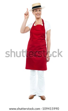 Female chef wearing hat pointing upwards, full length portrait