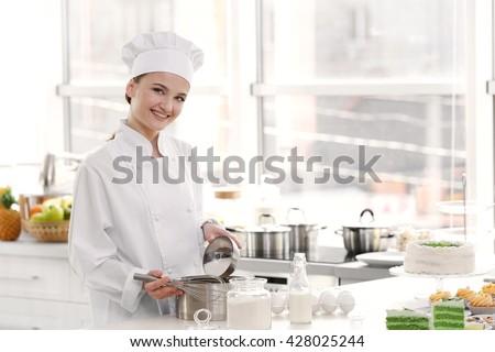 Female chef working at kitchen - stock photo