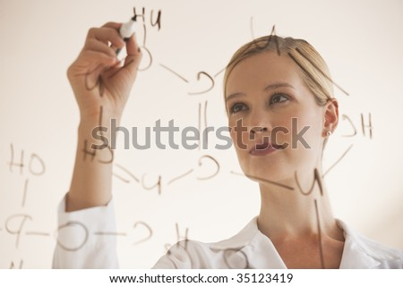 female chemist drawing chemical formulas on clear board