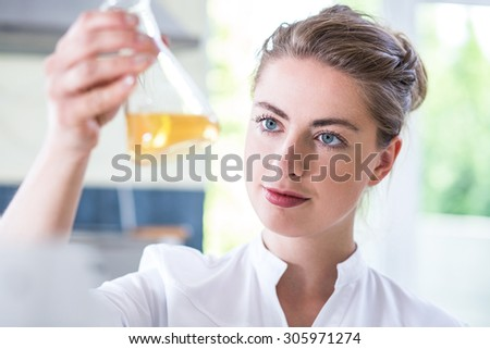 Female chemist holding flask with yellow liquid - stock photo