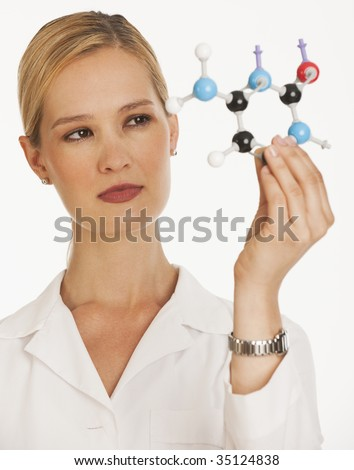 female chemist holding up molecules and looking at them