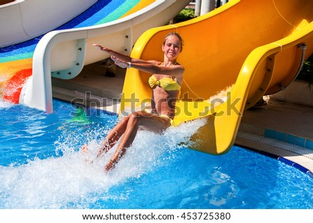 Female child on water slide at aquapark . Child pull your arms forward. There are some water slides with flowing water in aqua park. Summer water park holiday. Happy summer. Outdoor.