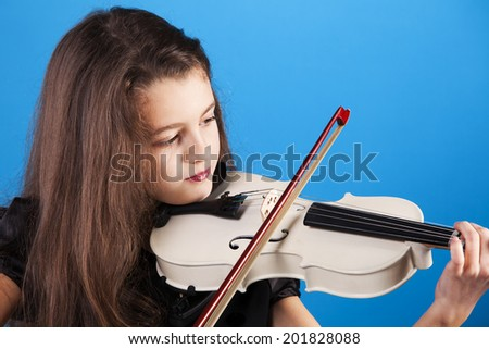 Female child playing the violin with blue background - stock photo