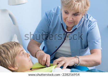 Female child's doctor examining schoolboy in hospital - stock photo