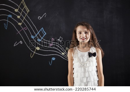 Female child who loves music next to a blackboard - stock photo