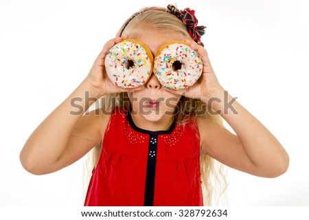 female child with long blonde hair and red dress playing with two  sugar donut with toppings putting them like eyes smiling happy children loving sweet concept and sugary nutrition - stock photo