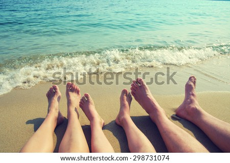 Female, children's and male feet on a beach against the sea in a summer sunny day. Family holiday - stock photo