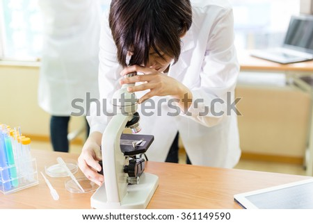 Female Chinese scientist looking into a microscope