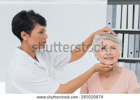 Female chiropractor doing neck adjustment in the medical office - stock photo