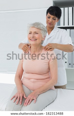 Female chiropractor massaging a senior womans shoulder in the medical office - stock photo