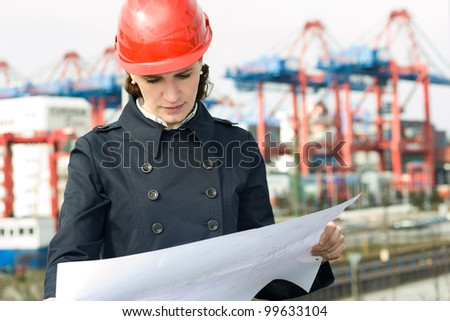 Female civil engineer wearing helm and checking the drawings in front of industry harbor background - stock photo
