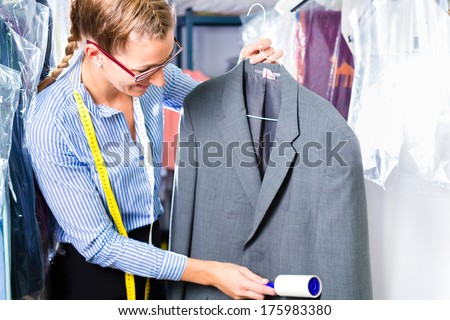 Female cleaner in laundry shop checking clean clothes removing lint with roller - stock photo