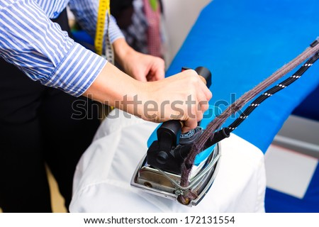 Female cleaner in laundry shop or textile dry-cleaning ironing jacket by hand with iron - stock photo
