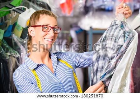 Female cleaner in laundry shop or textile dry-cleaning next to clean clothes in garment bags - stock photo