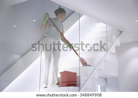 Female cleaner works in a modern home / office environment mopping the stairs - stock photo