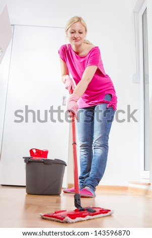 Female cleaning and mopping floor at home. - stock photo