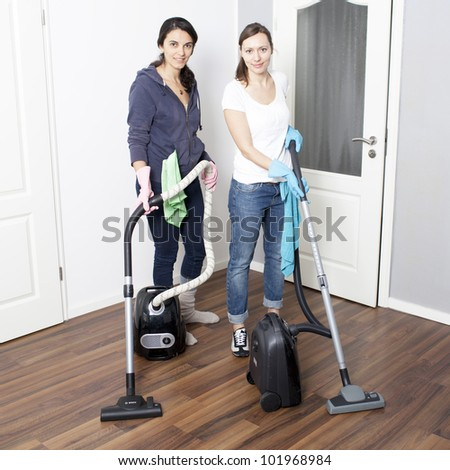 Female cleaning team vacuums a flat