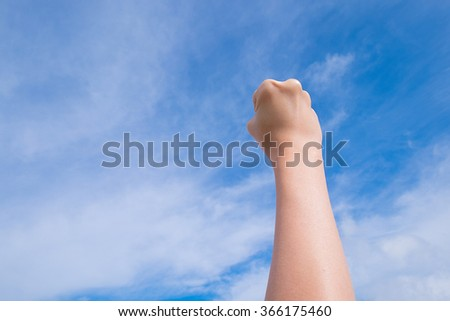 Female clenched fist on blue sky background