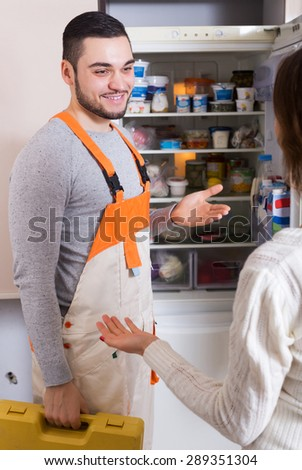 Female client and smiling warranty service man near fridge at kitchen