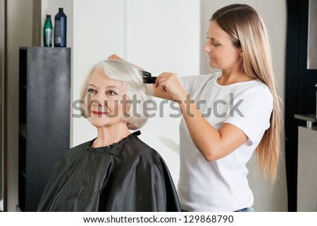 Female client having hair straightened by hairstylist at salon - stock photo