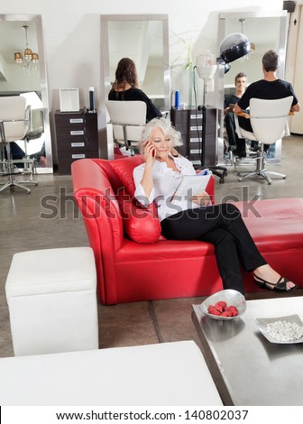 Female client holding magazine while on call with customers in background at salon