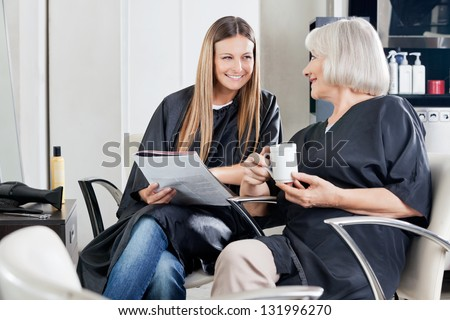 Female client's with magazine and cup conversing at beauty parlor - stock photo