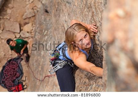 Female climber and her partner rock climbing - stock photo