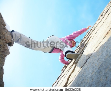 Female climber ascending the mountain from canyon - stock photo