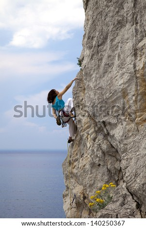 Female climber climbs the natural rock.