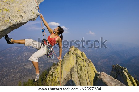 Female climber rappelling from the summit of an overhanging cliff. - stock photo