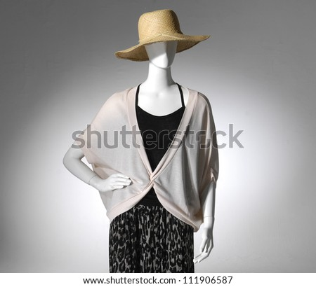 female clothes in hat on a mannequin on light background