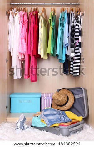 Female clothes in wardrobe and suitcase in room - stock photo
