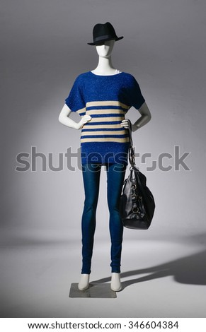 female clothing in jeans with hat ,bag on mannequin-light background - stock photo